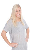 Blond Woman in Studio with Hands on Hips. Portrait of Smiling Blond Woman Wearing Grey T-Shirt with Hands on Hips Standing in Studio with White Background Stock Photos