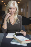 Blond woman studying. Books in library royalty free stock photography