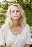 Blond woman in summer daydreaming Stock Images