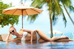Blond woman sunbathing on an infinity pool Royalty Free Stock Photography