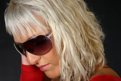 Blond woman in sunglasses. Side portrait of young blond woman in dark sunglasses, black background Royalty Free Stock Photos