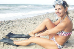 Blond woman with swimming goggles and flippers on the beach. Portrait of beautiful blond woman with swimming goggles and flippers on the beach Stock Photography