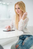 Blond Woman at the Table with Tablet Computer Royalty Free Stock Images