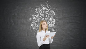 Blond woman with a tablet near chalkboard with dollar signs. Portrait of blond woman holding white tablet and standing near chalkboard with shining dollar signs Stock Photos