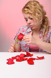 Blond woman taking petals of a rose Stock Photography
