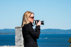 Blond woman taking photographs Stock Photography