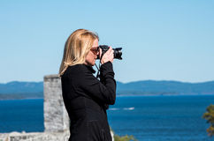 Blond woman taking photographs Royalty Free Stock Photography