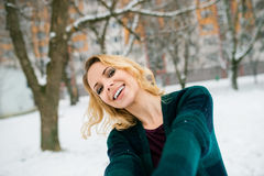 Blond woman taking selfie outside in winter nature Royalty Free Stock Photo