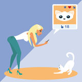 Blond woman is taking a snapshot of the cat for Royalty Free Stock Photography