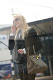 Blond woman talking on mobile phone outdoors Stock Photos