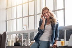 Blond woman talking per mobile phone near window Royalty Free Stock Photo
