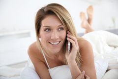 Blond woman talking on the phone lying in bed Royalty Free Stock Photography
