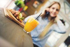 Blond woman talking on the phone at the table in a cozy cafe in the style of Provence. On the table a glass of juice and sweet wafer, the focus is positioned Stock Photography