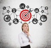 Blond woman, target and network. Portrait of a blond woman. She is standing near a concrete wall. There is a red target and a network sketch on it royalty free stock photography