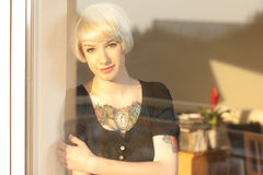 Blond woman with tattoo. Attractive blond woman with tattoo on chest and arm looking out of house window Stock Photo