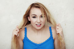 Blond woman teenage girl showing her damaged dry hair Royalty Free Stock Photo
