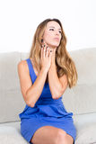 Blond woman with throat problems on coach Royalty Free Stock Image