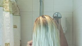 Blond woman touching her hair, water falling down from shower head in bathroom and wet her hair with water, body care concept.  stock video footage