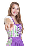 Blond woman in a traditional purple dress pointing at camera Royalty Free Stock Image