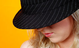 Blond woman with trendy hat. Portrait of young blond woman with trendy black hat looking downwards, yellow background with copy space Royalty Free Stock Photo