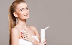 Blond woman using moisturizer. Royalty Free Stock Image