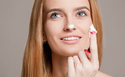 Blond woman using moisturizer. Portrait of a gorgeous young blond woman using moisturizer Royalty Free Stock Images