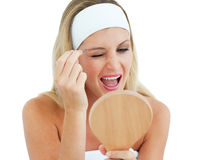 Blond woman using tweezers. Against a white background Stock Images