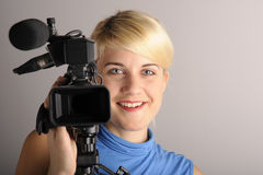 Blond woman with video camera Royalty Free Stock Photos