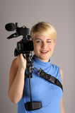 Blond woman with video camera Stock Images