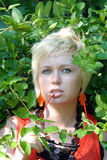 Blond woman with vines. Blond woman outdoors standing in green vines Royalty Free Stock Photos