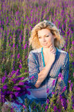 Blond woman in violet field Royalty Free Stock Image