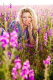 Blond woman in violet flowers Stock Photography