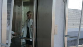 Blond woman waiting in front of an elevator and walking in