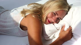 Blond woman waking up and smiles at camera stock video