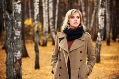 Blond fashion woman walking in autumn forest Stock Images