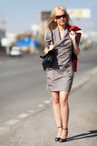 Blond woman walking on the street Stock Photography