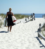 Blond Woman Walking to Beach. Blond Woman is walking on a sandy path to the Beach.  The sky is blue and cloudless Stock Photo