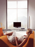 Blond woman watching TV. Lying on sofa in a living-room royalty free stock image