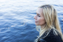 Blond woman by the waterfront Royalty Free Stock Images