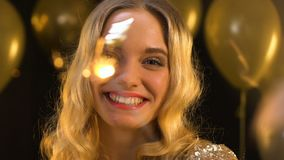 Blond woman waving bengal light under falling confetti, having fun at party. Stock footage stock footage