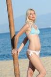 Blond woman wear bikini leaning on a wooden column Royalty Free Stock Photography