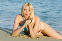 Blond woman wear bikini lying on sand Royalty Free Stock Images