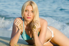 Blond woman wear bikini lying on sand Stock Images