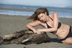 Blond woman wear black bikini lean on a tree trunks Royalty Free Stock Photos