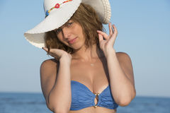 Blond woman wear blue bikini and white hat standing at the sea. Blond woman wear blue bikini and white hat, clear sky and sea as background, model facing the Royalty Free Stock Photo