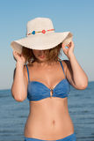 Blond woman wear blue bikini and white hat standing at the sea Royalty Free Stock Photo