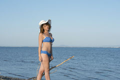 Blond woman wear blue bikini and white hat standing at the sea Stock Photo