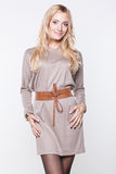 Blond woman  wearing beige dress with belt Stock Photography
