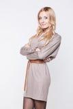 Blond woman  wearing beige dress with belt Royalty Free Stock Photo
