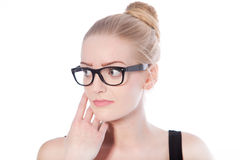 Blond woman wearing black framed eyeglasses. Portrait of a beautiful young blond woman, with loop of hair, wearing black framed eyeglasses, looking to the right Royalty Free Stock Photos